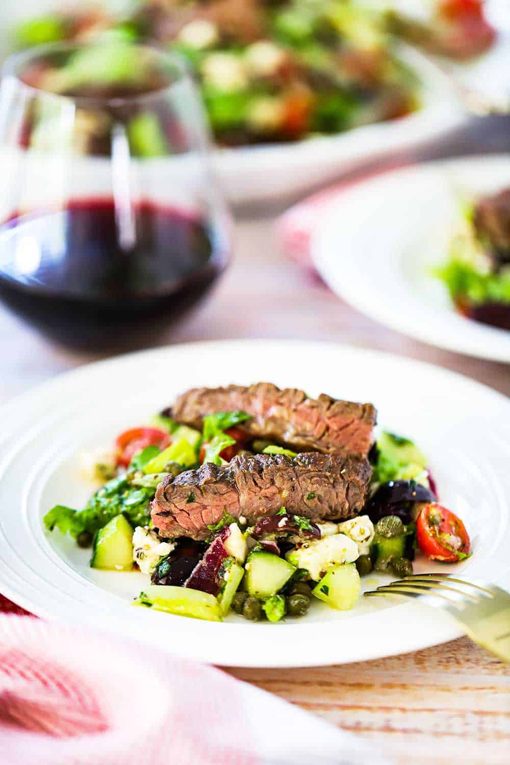 An individual plate filled with Greek salad with grilled meat sitting next to a glass of red wine.