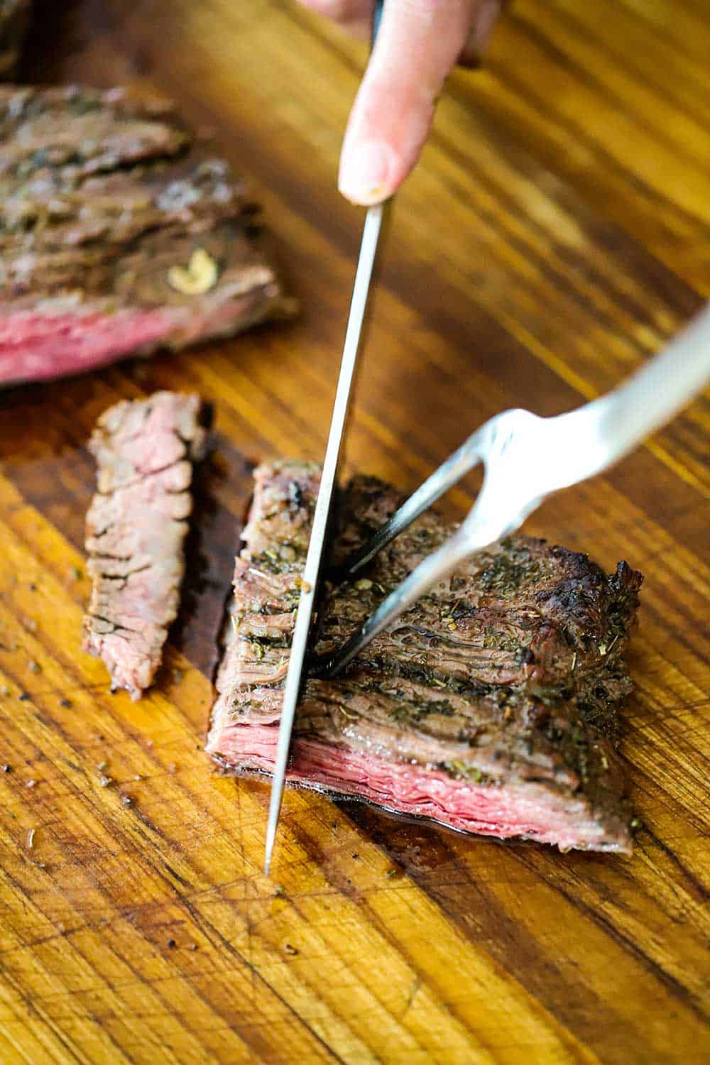 A hand using a carving knife and fork to slice a piece of grilled skirt steak against the grain to form bite-size strips.