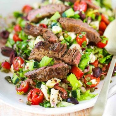 A large oval platter filled with a Greek salad and grilled steak with two large gold spoons on the side.