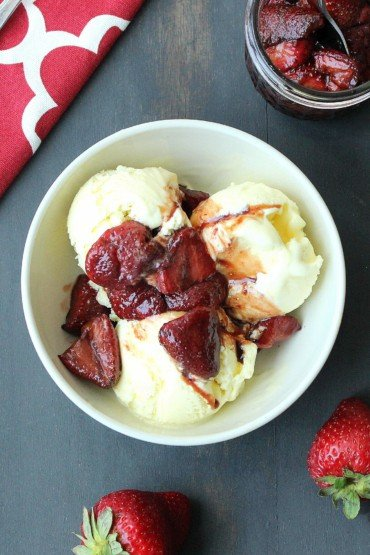 Olive Oil Ice Cream with Roasted Balsamic Strawberries next to a red patterned napkin