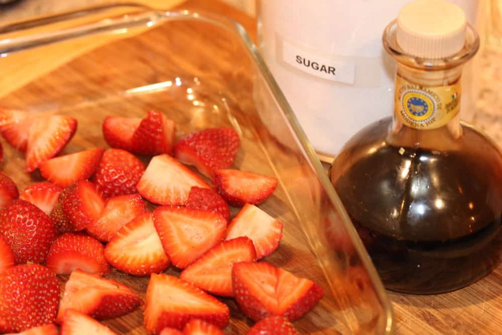 A glass dish with cut strawberries next to a jar of olive oil and a jar of sugar
