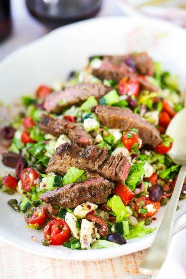 A Greek salad on a large oval platter topped with strips of grilled meat with two gold serving spoons on the side.