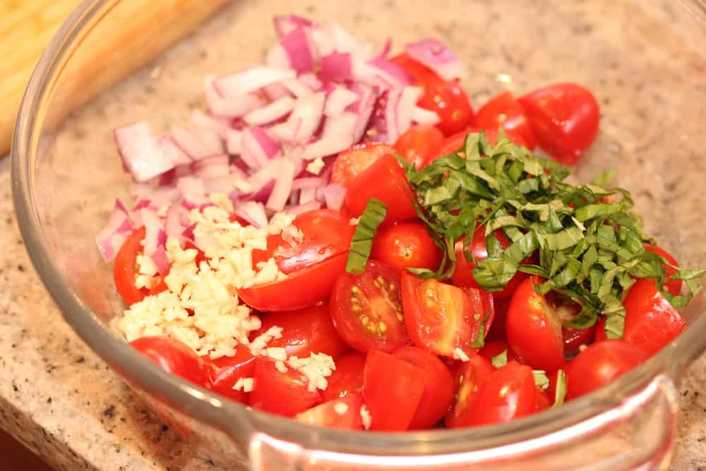 A glass bowl containing sliced cherry tomatoes, chopped red onion, minced garlic, and fresh herbs.