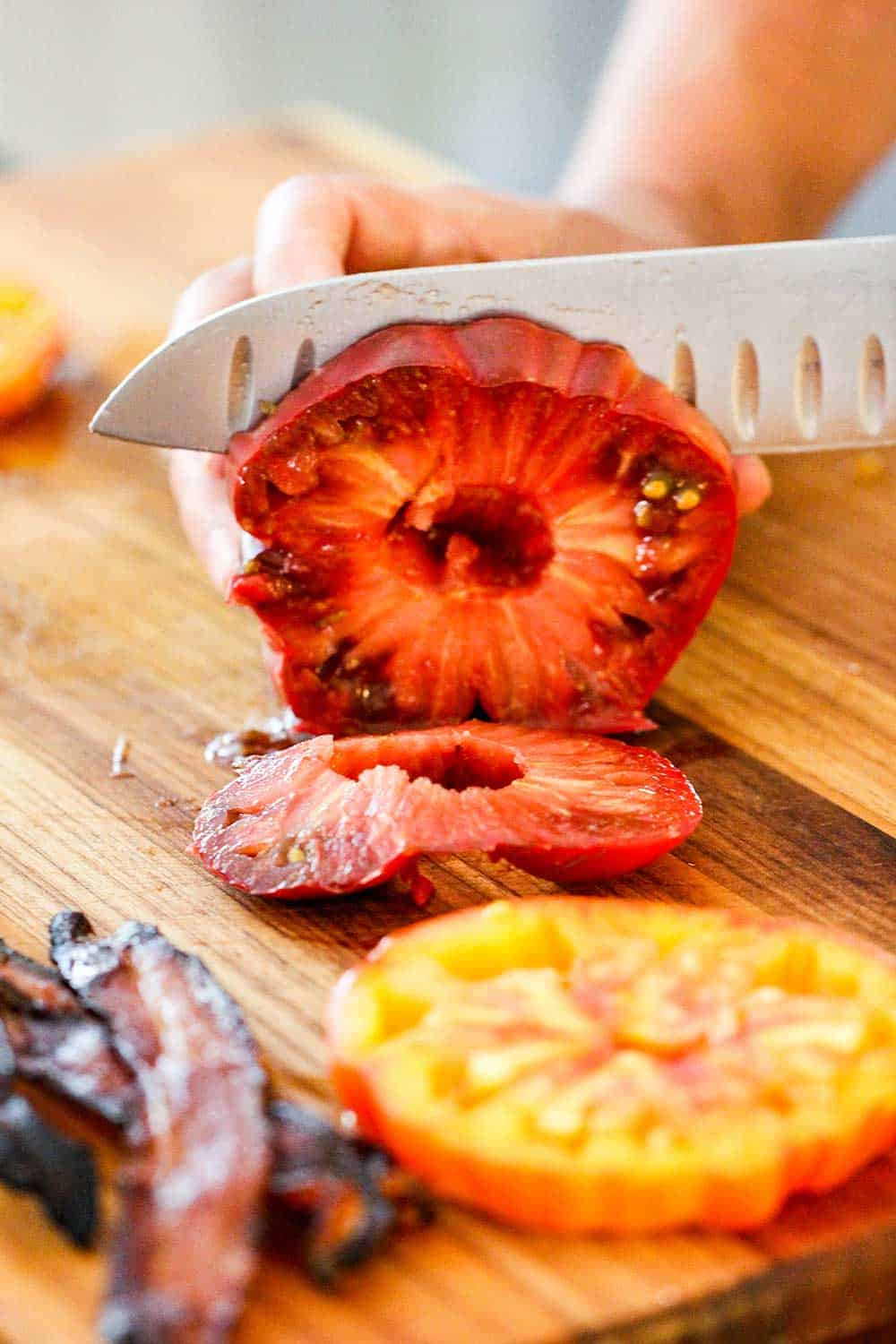 A knife slicing into a red heirloom tomato for classic BLT with garlic basil aioli