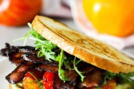 A classic BLT sandwich with garlic aioli on a white plate with two tomatoes in the background.