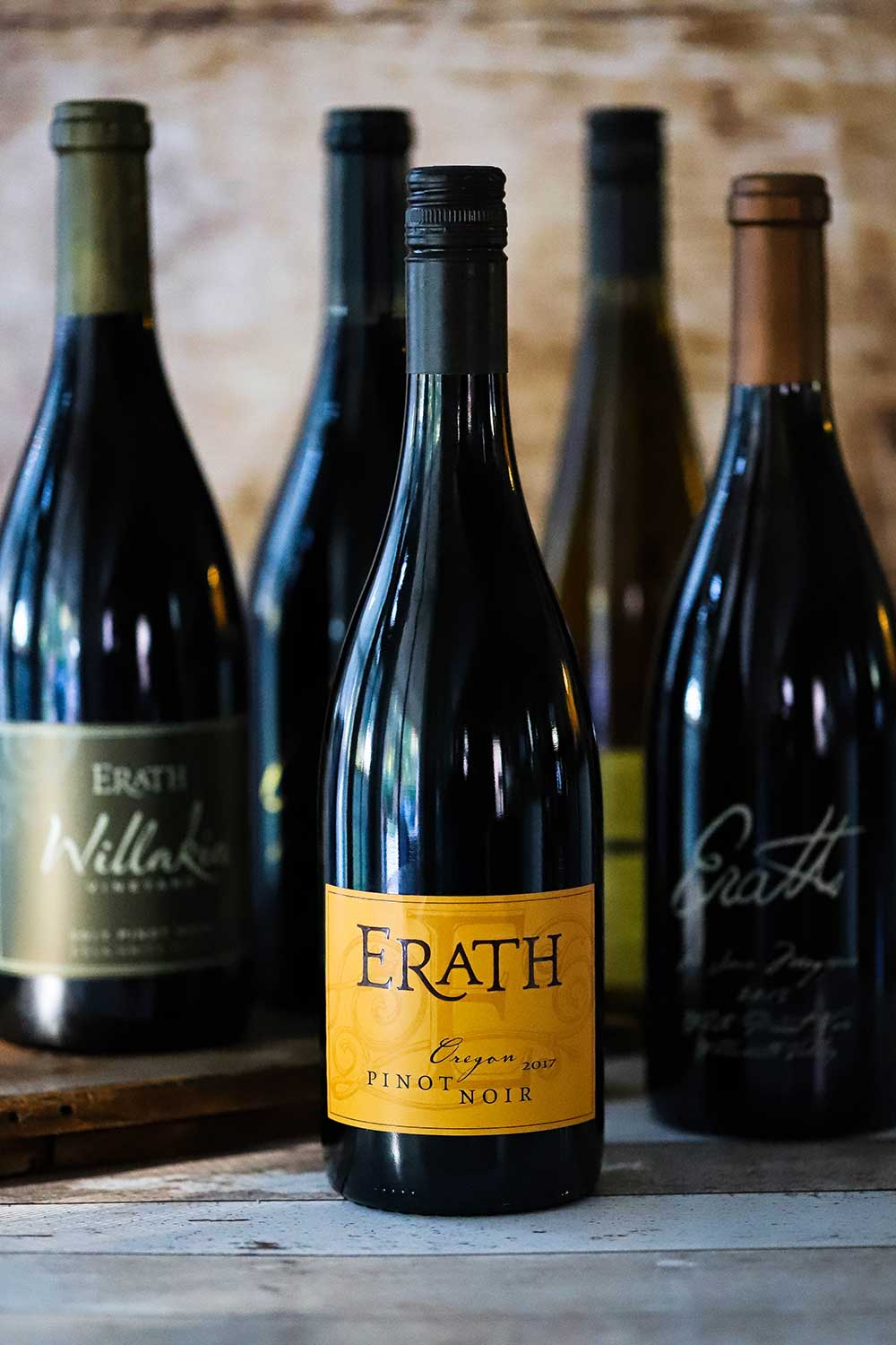 A collection of Erath Pinot Noir wine bottles standing next to each other.