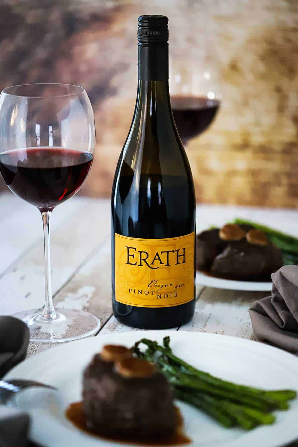 A bottle of Erath Oregon Pinot Noir sitting next to a plate of filet mignon and roasted asparagus.