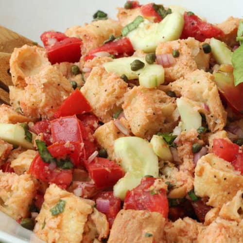 Panzanella (Bread and Tomato Salad) in a white bowl with a wood spoon