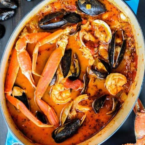 Classic cioppino in a large blue Dutch oven pot