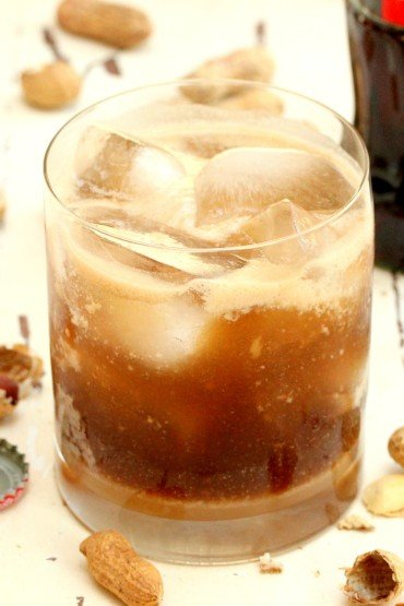 a rocks glass filled with a Tallulah Cocktail sitting next to peanuts and a bottle of Coca-Cola.