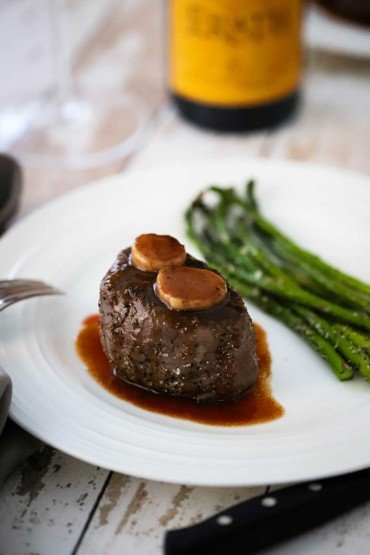 A white plate holding a filet mignon with classic Bordelaise sauce and a side of roasted asparagus.
