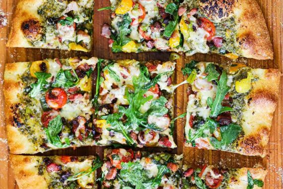 An overhead view of Pesto Pizza with Pancetta, Tomatoes and Arugula sitting on a cutting board next to sliced cherry tomatoes.