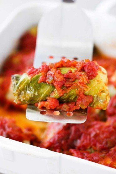 A metal spatula holding up a stuffed cabbage roll over a dish of the same.