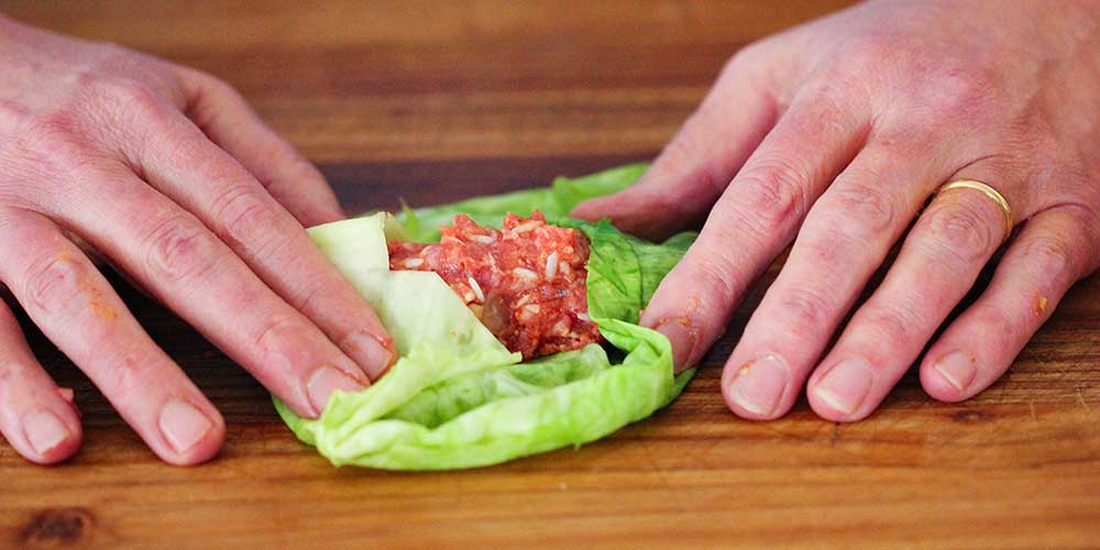 Two hands folding in the sids of a cabbage leaf over a meat filling.