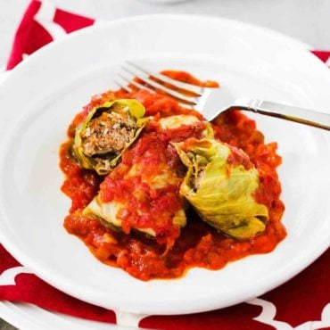 A white dinner plate filled with stuffed cabbage rolls with one split in half next to a fork.
