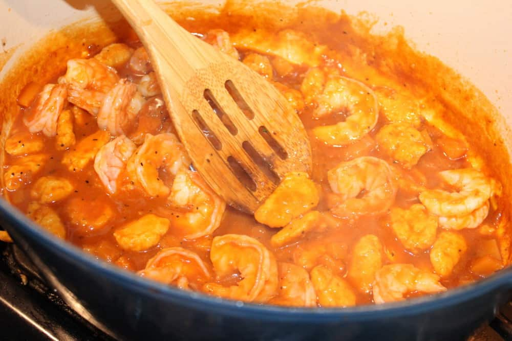 Dumplings and shrimp in sauce in a large blue pan being mixed with a wood spoon