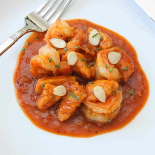 Pumpkin Gnocchi with Shrimp in a white bowl with a fork and knife
