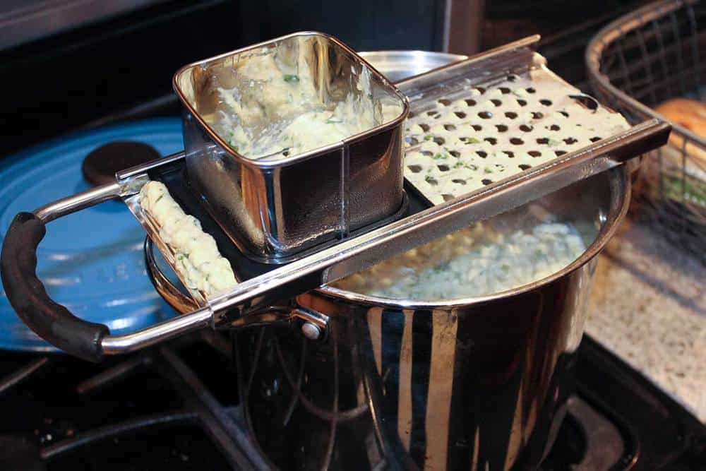 Spaetzle dough being dropped into boiling water from a spaetzle maker