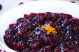A white bowl containing Maple Orange Cranberry Sauce next to sliced oranges and cranberries.