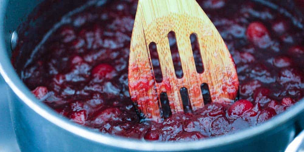 A wooden spoon in a pan of maple orange cranberry sauce.