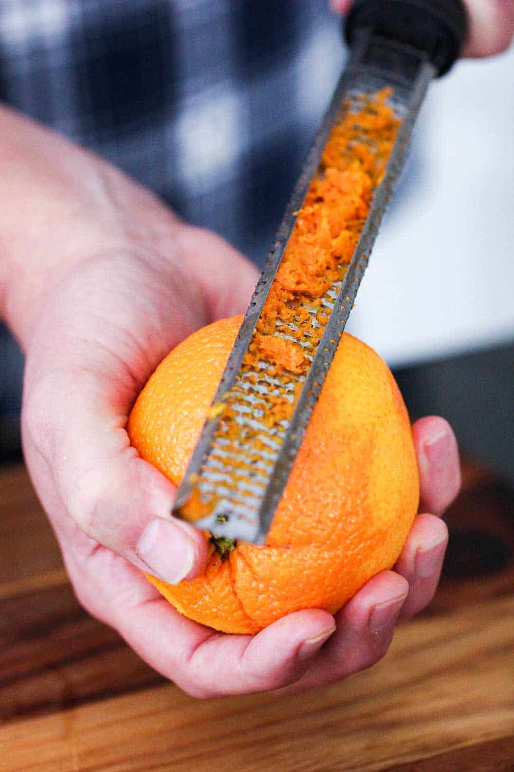 One hand holding an orange while the other hand is use a zester to zest the orange.