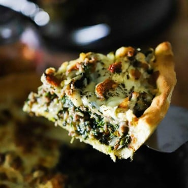 A slice of deep-dish pizza with sausage and spinach being lifted from the pan with a spatula.