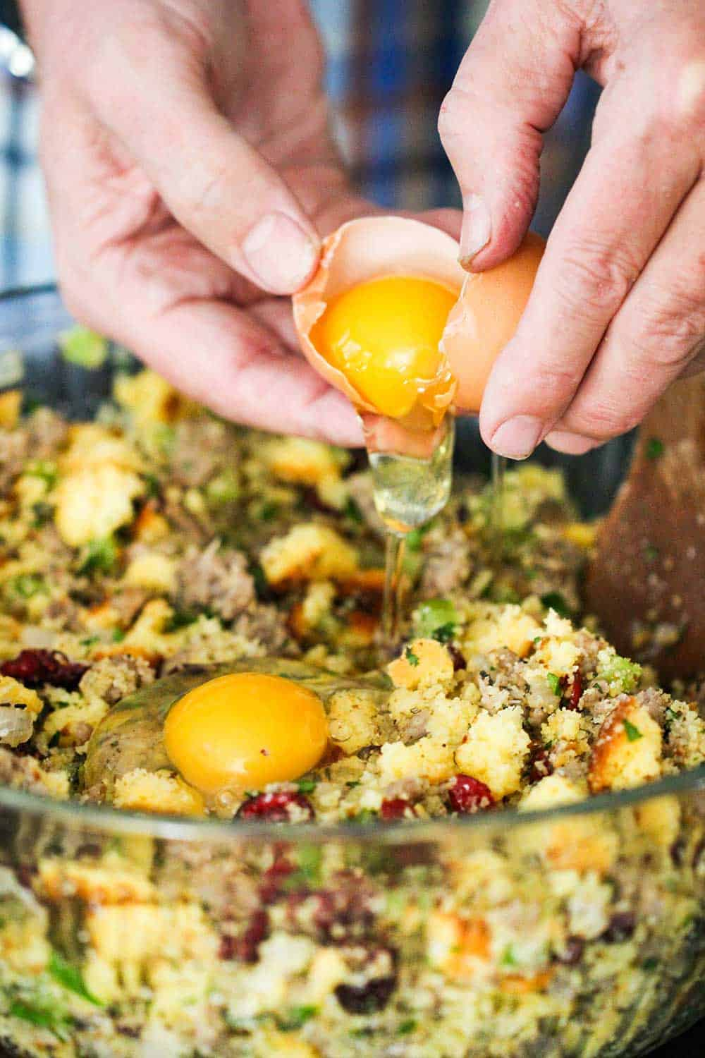 Two hands cracking an egg into a large glass bowl of cornbread dressing with sausage and cranberries.