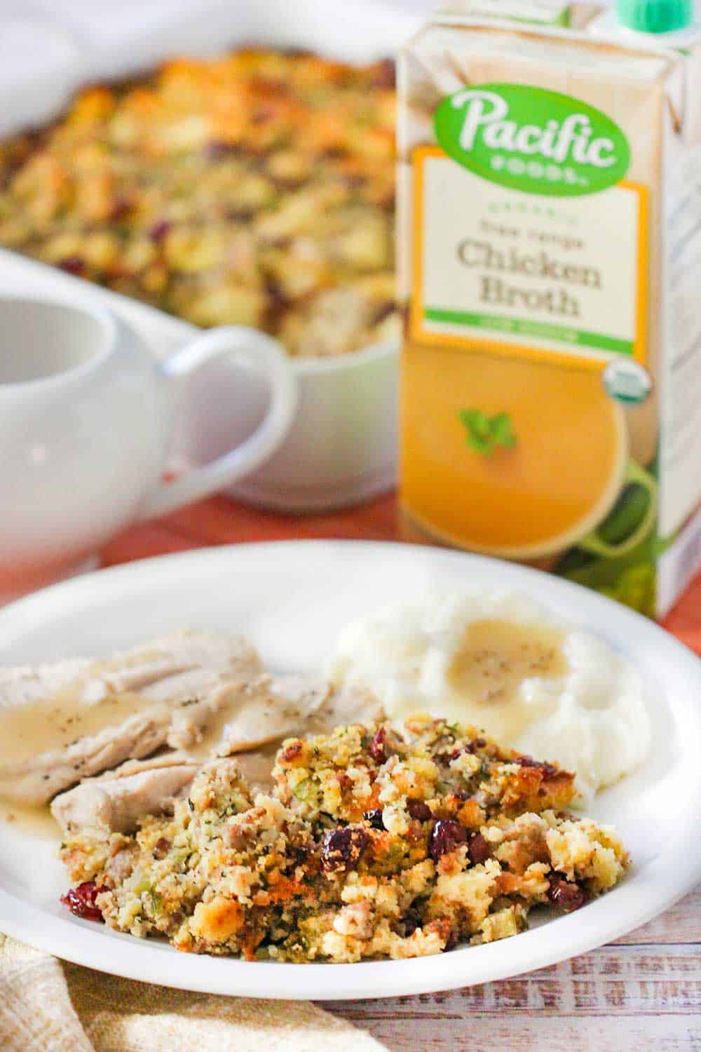 A plate full of roasted turkey, mashed potatoes and cornbread dressing with a box of broth next to it.