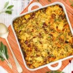 A square dish filled with cornbread dressing with sausage and cranberries.