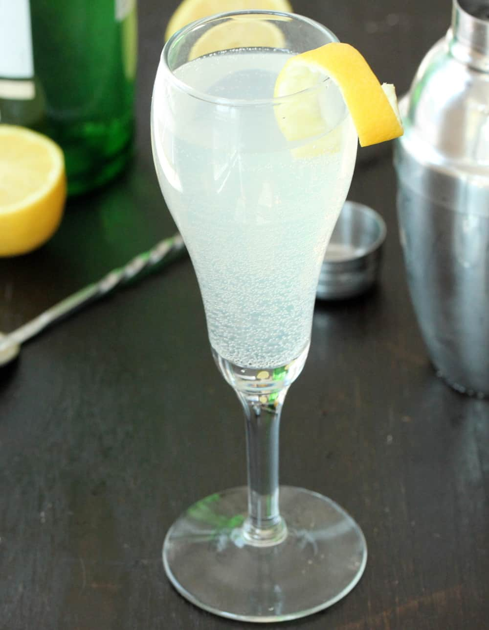 A Champagne flute filled with a French 75 cocktail with a lemon twist on it next to a cocktail shaker.