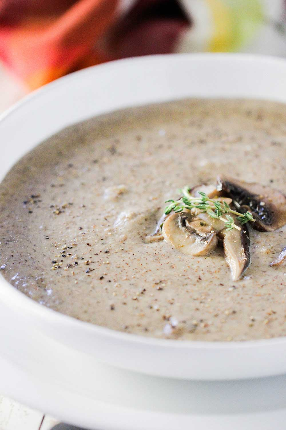 A close up view of a white soup bowl holding cream of mushroom soup with sautéed mushrooms on top.