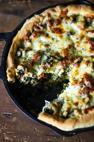 A deep dish pizza with sausage and broccoli in a cast-iron skillet with a slice cut out.