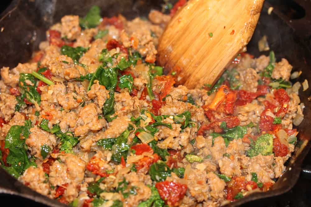 A wooden spoon stirring sautéd sausage with broccoli rabe and sun-dried tomatoes for a deep dish pizza filling.
