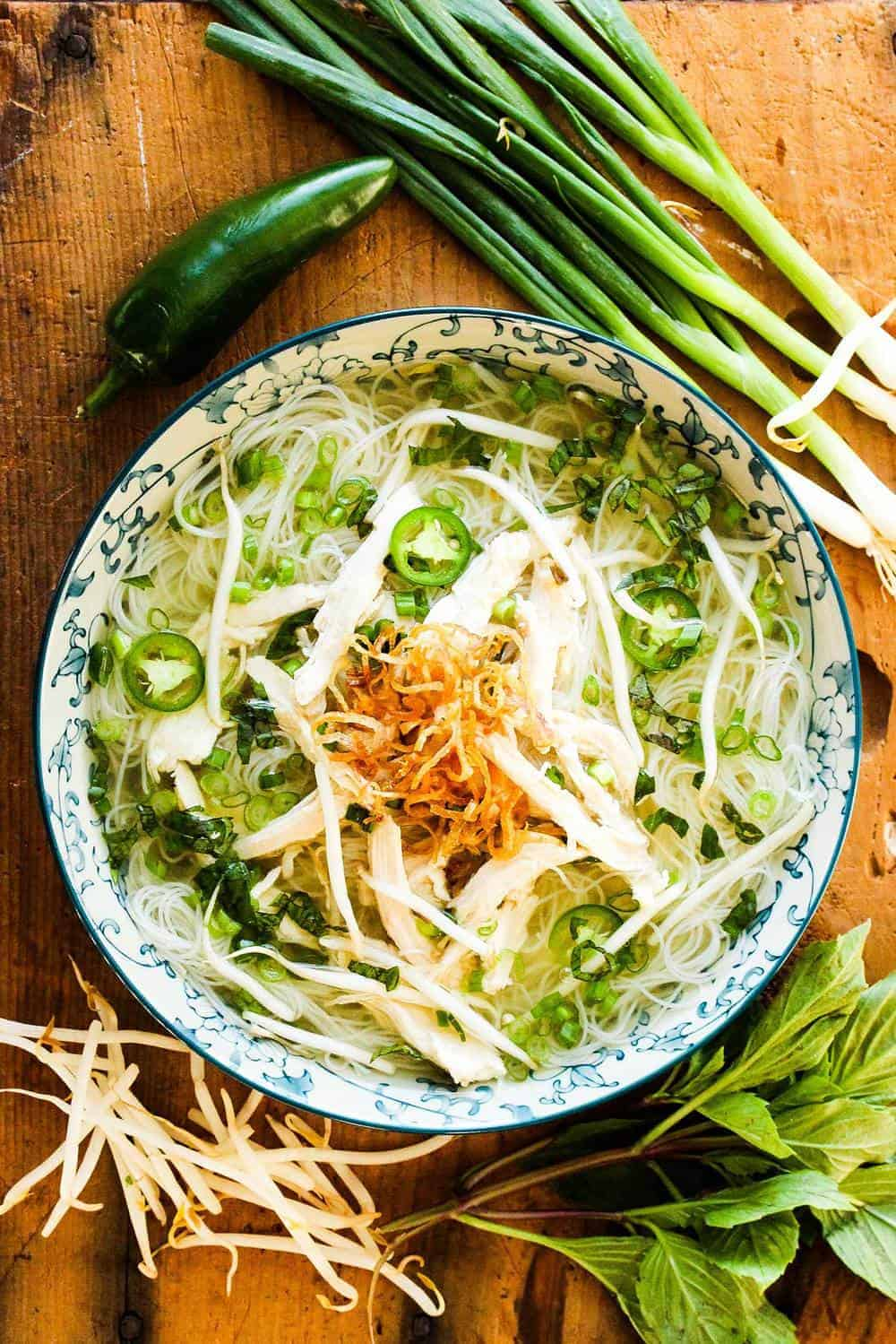 A bowl of pho and scallions and shallots on the side