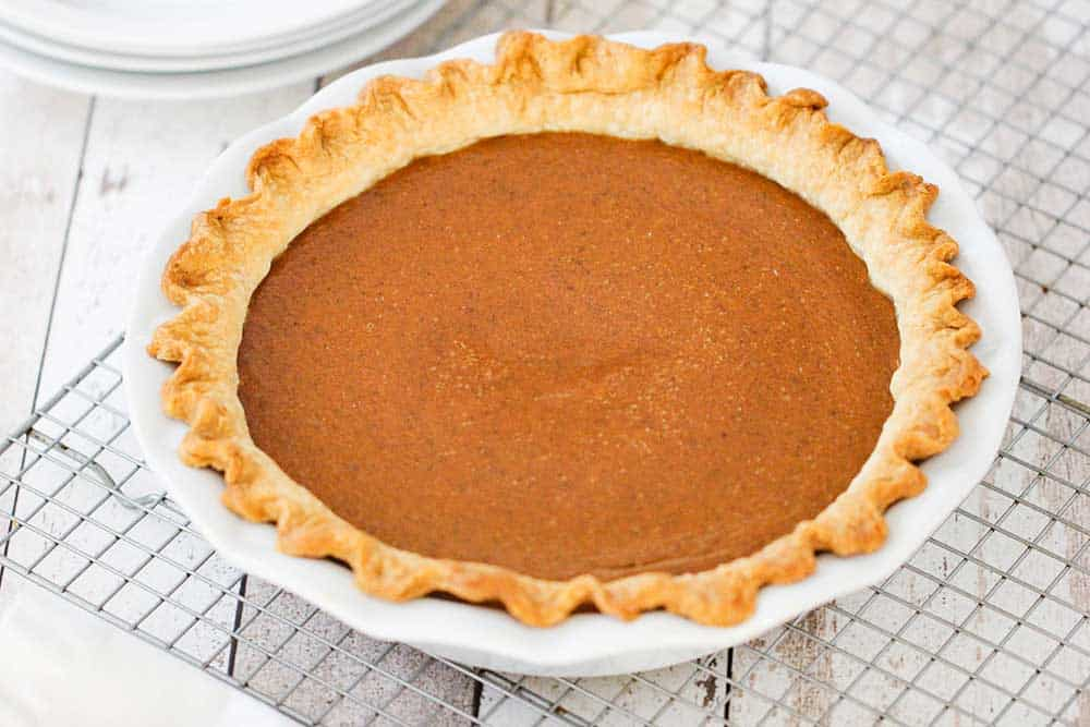 A fully cooked classic pumpkin pie in a white pie dish sitting on a baking rack.