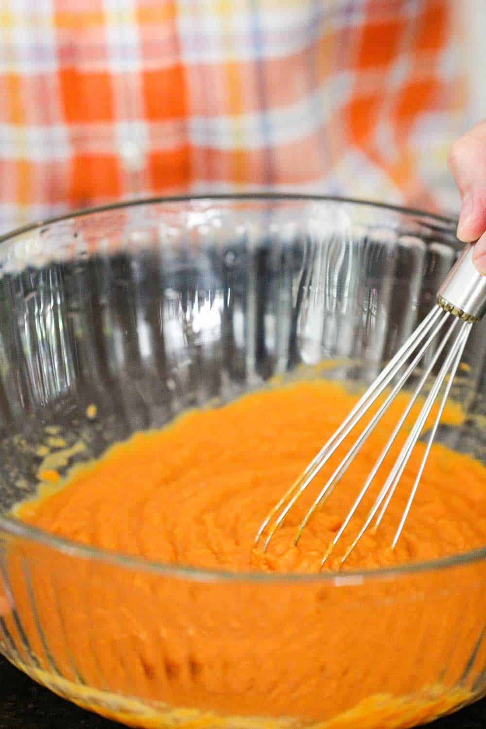 A large bowl filled with pumpkin puree, with a hand holding a whisk in the bowl.