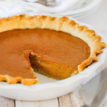 A pumpkin pie with a slice missing in a white pie dish.