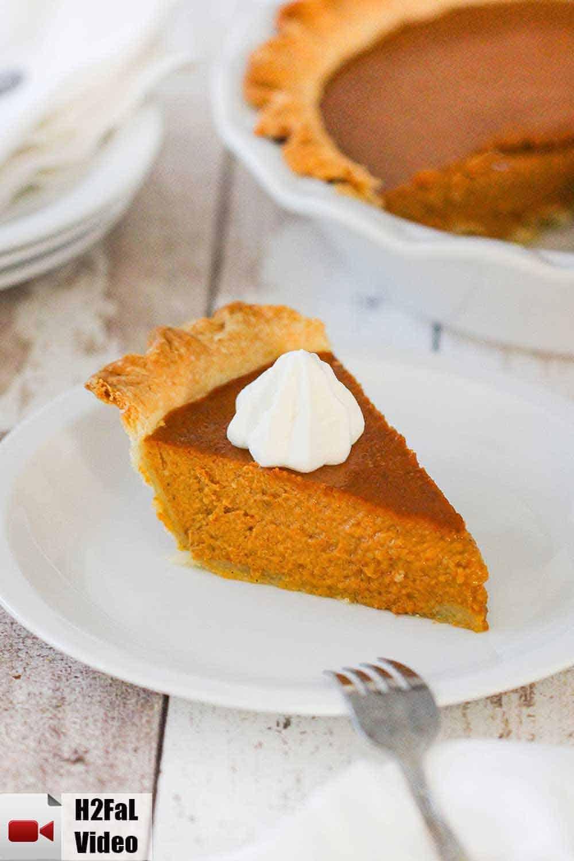 A slice of pumpkin pie on a white plate next to a whole pumpkin pie.