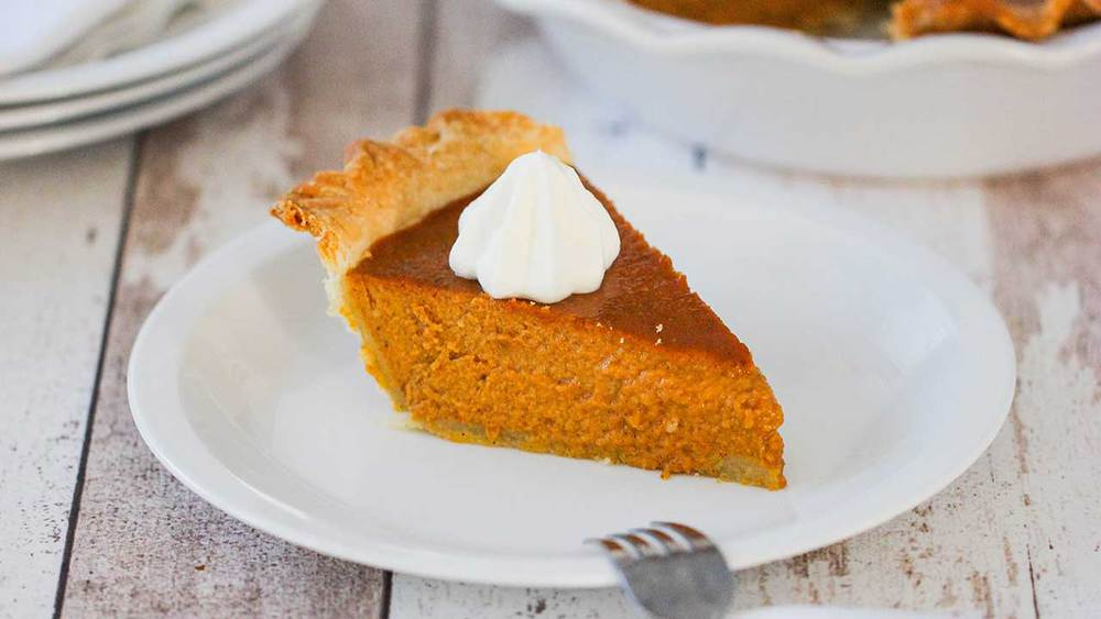 A slice of pumpkin pie with a dollop of whipped cream on top on a white dessert plate.