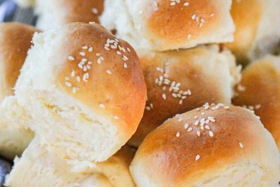 A basket lined with a grey cloth filled with homemade dinner rolls.