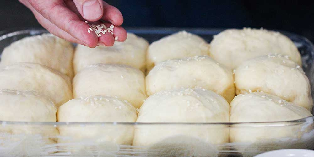 A hand sprinkled white sesame seeds onto uncooked dinner rolls dough in a glass baking dish.