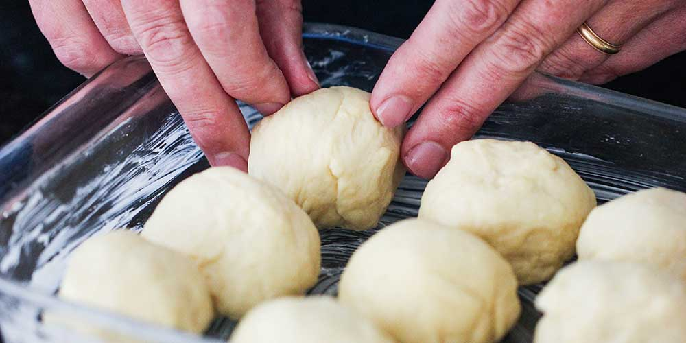 Two hands placing a ball of dough into a dish next to other balls of dough.