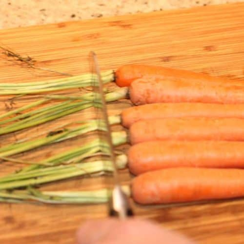 A hand holding a knife trimming the carrot tops on a wood cutting board