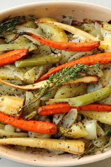 Roasted root vegetables in a white baking dish.