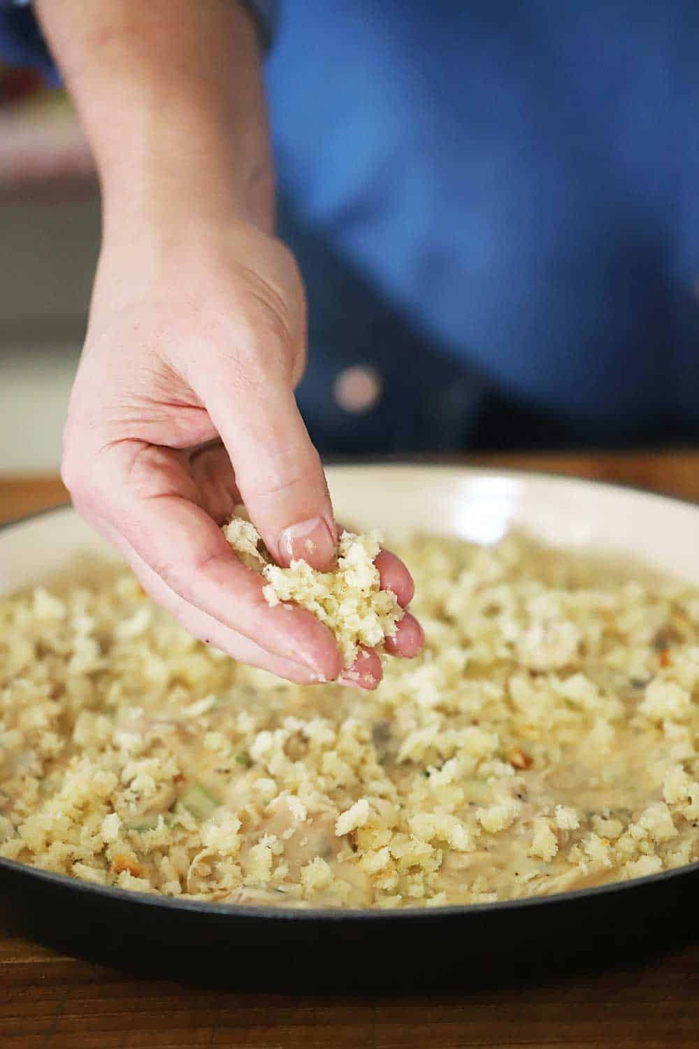 A person sprinkling fresh bread crumbs over the top of an uncooked oyster casserole in a black oval baking dish.