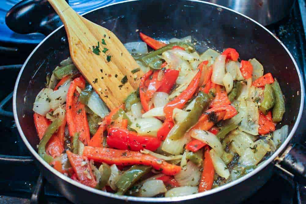 Red and green bells peppers and sliced onion and herbs cooking in a large skillet with a wooden spoon.
