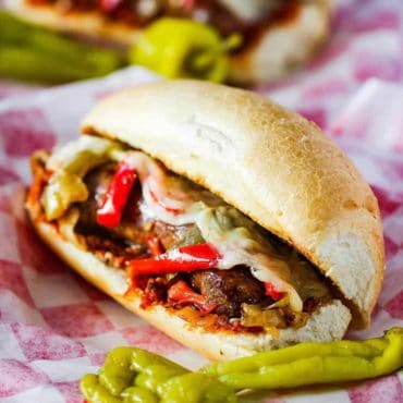 Sausage and Peppers Hero on a checkered napkin.