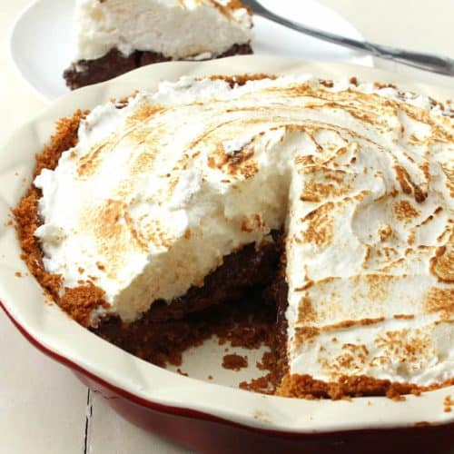 S'Mores Pie in a white pie dish with a slice of pie on a white plate in the background