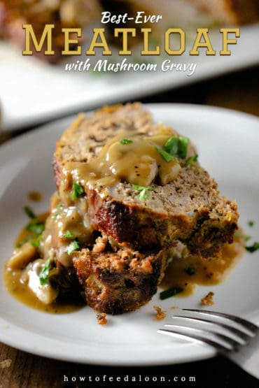 Two slices of meatloaf on a white plate with mushroom gravy poured over the top.