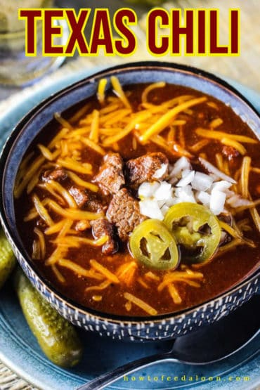 A large blue bowl filled with Texas chili topped with cheese, onions, and jalapenos next to a glass of beer and a jar of pickles.